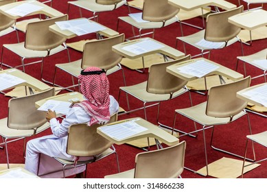 DAMMAM, SAUDI ARABIA -  JULY 7:  Saudi student wearing traditional thobe and headdress fills in his answer key in preparation for an examination on 7 July, 2015 in Dammam, Saudi Arabia.