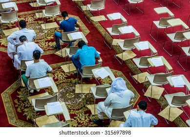 DAMMAM, SAUDI ARABIA -  JULY 8:  On a red carpet with rows of desks and chairs, college students prepare for an exam on 8 July, 2015 in Dammam, Saudi Arabia.