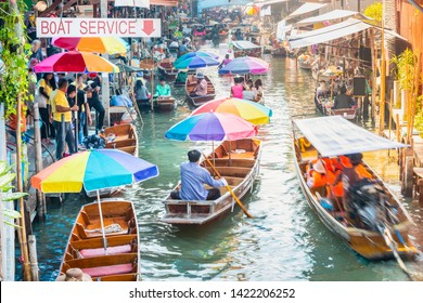 Damnoen Saduak Floating Market, tourists visiting by boat. The text on boats translate into English is coconut ice cream, mango and sticky rice, grilled chicken and pork. Located in Bangkok, Thailand.