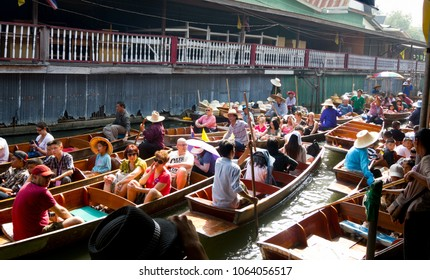 Damnoen Saduak, Thailand - December 14th, 2012: Tourists and crowded boats passing eachother by on the floating market, one of the main attractions near Bangkok
