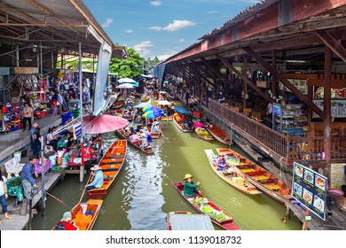 DAMNOEN SADUAK, THAILAND - JUNE 19, 2018: Floating market with fruits, vegetables and different items sold from small boats, in Damnoen Saduak, Thailand
