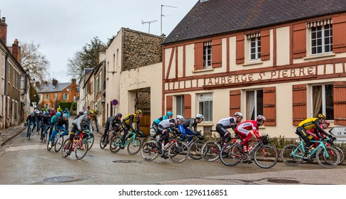 Dampierre-en-Yvelines, France - March 4, 2018: The Peloton passes in front of  traditional buildings on a small street in a French village during Paris-Nice 2018