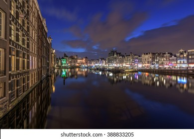 The Damrak in Amsterdam in high detail, with reflection after sunset.