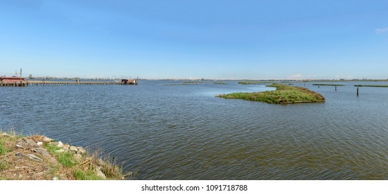 dams, bradwalk and old traditional fishing huts on the brackish lagoon, shot in bright spring sun light at Comacchio, Ferrara,  Italy