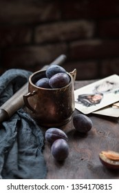 Damson plums are in the ancient copper cup.