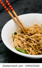 Dan Dan Noodle vertical view. Dan Dan Noodles is a spicy Szechuan cuisine dish commonly found in chinese street food. Ingredients include thick rice noodles, sichuan pepper, chili oil and ground pork.