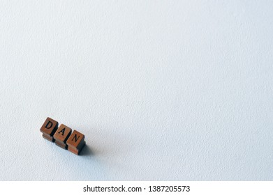 Dan - popular boys name formed of wooden blocks on a white background. Dan common male name.