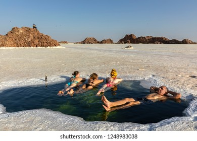 DANAKIL DEPRESSION, ETHIOPIA-NOVEMBER 15, 2018: Tourists are happy to swim in the washouts in the salt lake. High salinity of water does not allow not only to drown, but even to plunge into the water