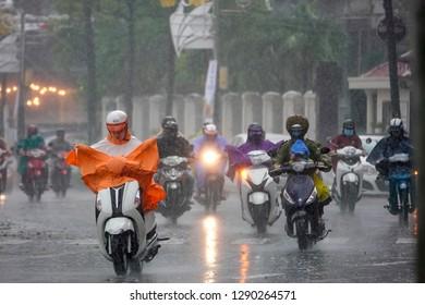 Danang city/Vietnam - June 2017: Group of Vietnamese people drive motorbike in heavy rain day, person wear helmet, raincoat move in raining and wind, in Danang city, Vietnam.