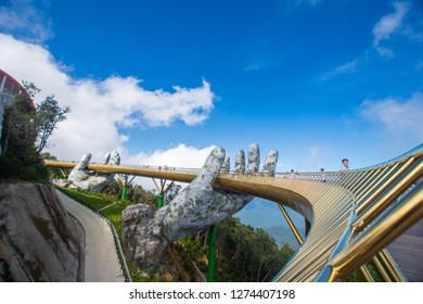 Danang, Vietnam - Dece 2, 2018: The Golden Bridge with blue sky on Ba Na Hill in Danang, Vietnam. Ba Na Hill mountain resort is a favorite destination for tourists for travel.