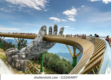 Danang, Vietnam - July 5, 2018: The Golden Bridge is lifted by two giant hands in the tourist resort on Ba Na Hill in Danang, Vietnam. Ba Na Hill mountain resort is a favorite destination for tourists