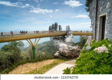 Danang, Vietnam - July 5, 2018: The panoramic view of Golden Bridge is lifted by two giant hands in the tourist resort on Ba Na Hill in Danang, Vietnam. Ba Na Hill mountain resort is a favorite destin