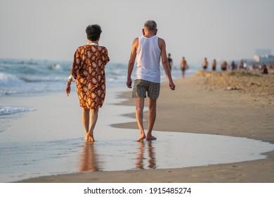 Danang, Vietnam - june 20, 2020 : Vietnamese man and woman relax on the beach near sea in the morning before sunrise on the city Da nang, Vietnam