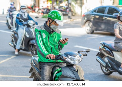 Danang, Vietnam - October 14, 2018: A young man on scooter, wearing a Grab green helmet and jacket, looks at his mobile phone. Grab app is a popular way of earning money & traveling in Southeast Asia.