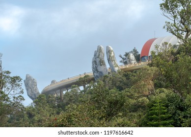 Danang, Vietnam - Sep 21, 2018: The Golden Bridge is lifted by two giant hands in the tourist resort on Ba Na Hill in Danang, Vietnam. Ba Na Hill mountain resort is a favorite destination for tourists