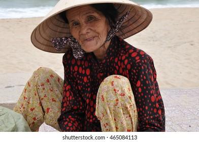 Danang, Vietnam-February 1, 2012: An elderly Vietnamese woman sits on a beach