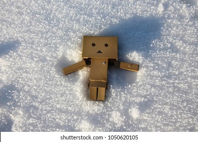 Danbo figure making a snow angel.