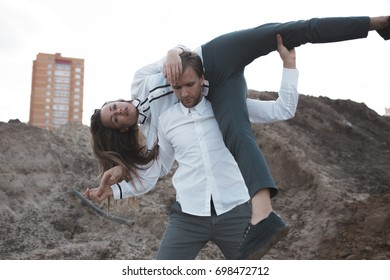 the dance of the body. slender girl with long hair and plastic guy dancing on a deserted wasteland. street style in clothes. in the background of panel high-rise buildings. urban style
