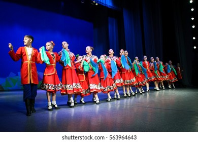 The dance of Cossacks - the guys in red clothes and girls with headscarves lined up in a row. Choreographic Festival, Tomsk, Russia, 2016