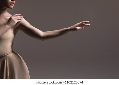 Dance forever! Tender hands of the young delicate gentle professional ballerina dancing on the isolated beige background indoors.