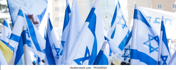 dance with the Israeli flags during the Jerusalem day (Israeli national holiday commemorating the reunification of Jerusalem) in a street of Jerusalem