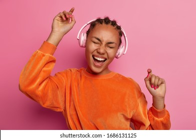 Dance with me. Upbeat dark skinned teenager raises arms, moves with rthythm of melody, feels energetic, dressed in bright orange jumper, has fun, isolated on pink background. Music brings joy