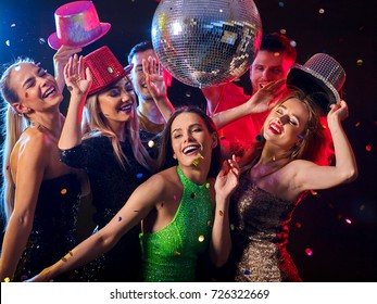 Dance party with group people dancing. Women and men have fun in night club. Happy girl on foreground and disco ball on background. Opening of a new strip club.