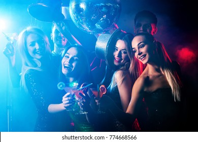 Dance party with group people dancing. Women and men have fun in night club. Happy girl on foreground and disco ball on background. Illumination from rays, special effects. Opening of new strip club.
