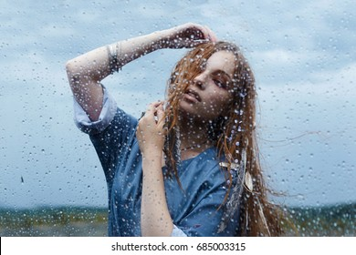 Dance in the rain.indian style beautiful dancing woman.raining weather lifestyle portrait of girl behind the wet glass