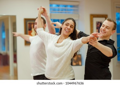 Dance teacher and ballroom dancers looking in mirror. Mixed race young woman dance with partner