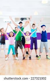 Dance teacher giving children Zumba fitness class in gym