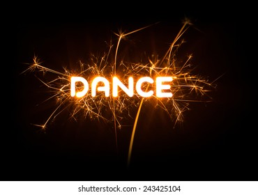 DANCE word in glowing sparkler on dark background.