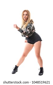 Dancehall female dancer wearing camouflage shirt and boots with clenched fist looking down. Full body isolated on white background.