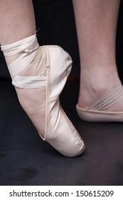 dancer in ballet shoes dancing in Pointe on a wooden floor