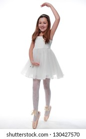 Dancer in ballet shoes is studying the art of ballet on white background