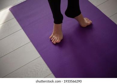dancer bare feet stand on a training mat close-up. Heels off the floor
