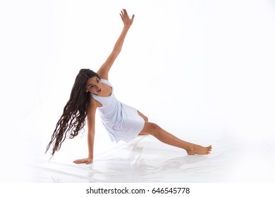 Dancer brunette girl with long hair in white dresses dances Contemporary in a studio on a white background