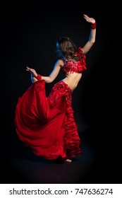 Dancer brunette girl with long hair in red oriental costume posing and dancing on black background in studio