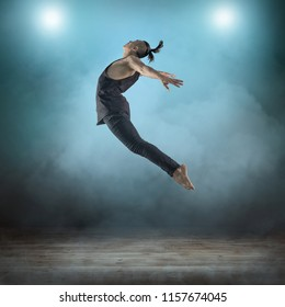 dancer in dynamic action figure pose under light on the grunge background.