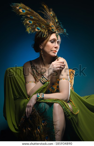 Dancer in exotic costume sits in armchair on dark background