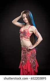 Dancer girl brunette with long hair in red oriental costume and mehendi on hand posing and dancing on black background in studio