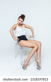 Dancer girl in short shorts on chair on light background.