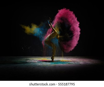Dancer moving in cloud of coloured dust on scene
