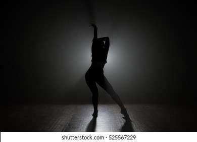 Dancer posing in the dark and smoke