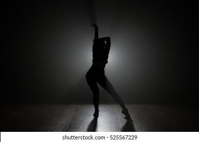 Dancer posing in the dark and smoke