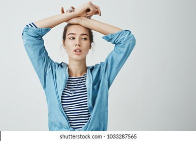 Dancer practices alone at studio. Portrait of beautiful sensual woman with bun hairstyle holding crossed arms on forehead and looking aside with tired and feminine expression, standing over gray wall