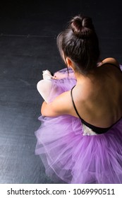 dancer in purple tutu preparing for performance