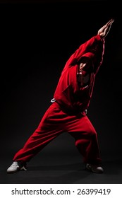 dancer in red clothes posing against black background