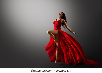 Dancer in Red Dress Jumping. Woman Ballerina Expressive Balance Dance Flying Fabric in Air. Fashion Model Dancing over Gray Studio Background