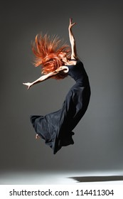 dancer with red hair jumping over dark grey background